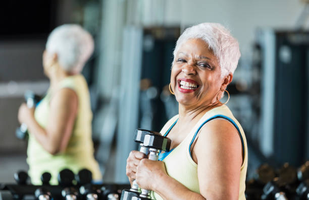 Senior African-American woman at gym lifting dumbbells stock photo