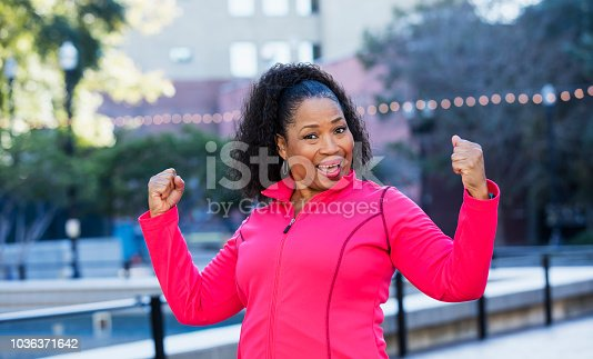 A senior African-American woman in her 60s wearing a pink sweatshirt, exercising in the city. She is smiling a the camera, flexing her biceps, showing her strength.