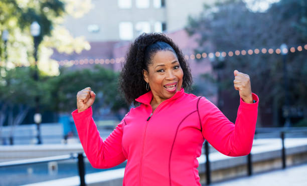 Senior African-American woman exercising in city A senior African-American woman in her 60s wearing a pink sweatshirt, exercising in the city. She is smiling a the camera, flexing her biceps, showing her strength. flexing muscles stock pictures, royalty-free photos & images