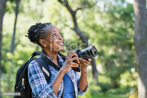 A senior African-American woman in her 70s enjoying the outdoors, hiking in a park, taking photographs. She is looking upward.