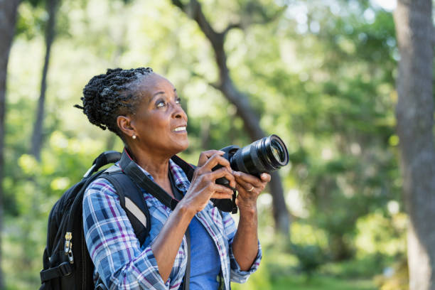 Senior African-American woman hiking, with camera A senior African-American woman in her 70s enjoying the outdoors, hiking in a park, taking photographs. She is looking upward. hobbies stock pictures, royalty-free photos & images