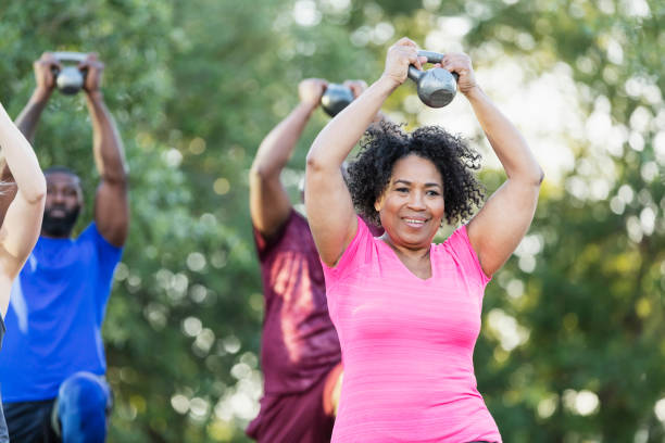 Senior African-American woman in exercise class A multi-ethnic group of people of mixed ages in an exercise class outdoors at the park, lifting kettlebells above their heads. The focus is on a senior African-American woman in her 60s. exercise class stock pictures, royalty-free photos & images
