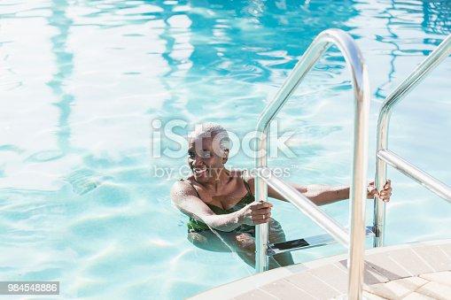 istock Senior African-American woman on swimming pool ladder 984548886