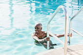A senior African-American woman in her 60s in a swimming pool, smiling as she climbs out using the ladder.