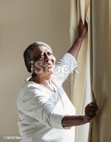 949450544istockphoto Senior African-American woman opening curtain 1128767594