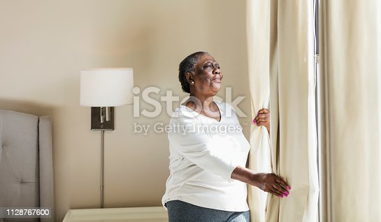 949450544istockphoto Senior African-American woman opening curtain 1128767600