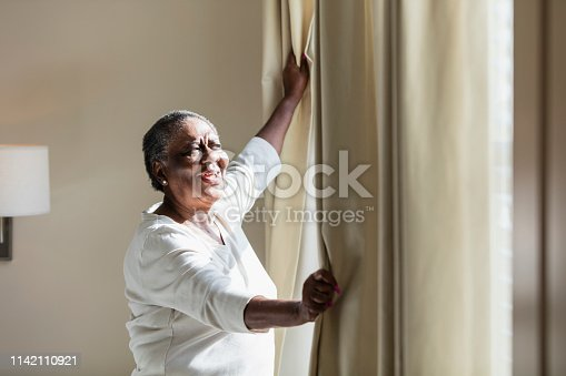949450544istockphoto Senior African-American woman opening curtain 1142110921