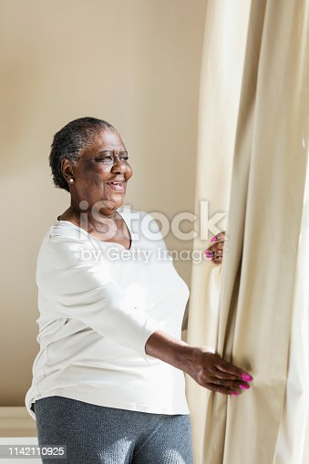 949450544istockphoto Senior African-American woman opening curtain 1142110925