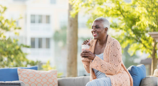 Senior African-American woman relaxing on patio A senior African-American woman in her 60s relaxing outdoors on her patio, sipping a cold, refreshing beverage through a straw. 65 69 years stock pictures, royalty-free photos & images