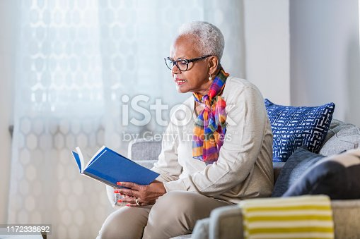istock Senior African-American woman sitting at home reading 1172338692