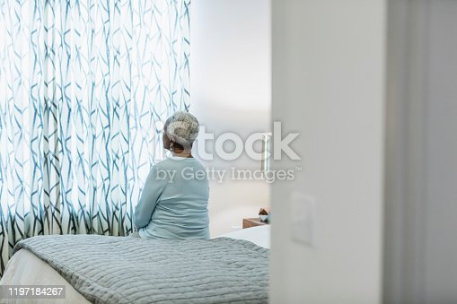 Rear view of a senior African-American woman in her 60s sitting on the edge of her bed, looking toward the window, thinking.