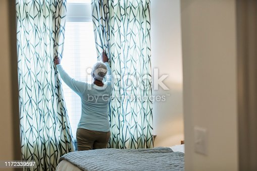 949450544istockphoto Senior African-American woman waking up, at window 1172339597