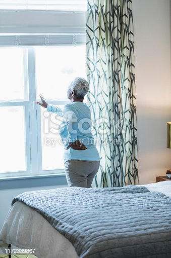 949450544istockphoto Senior African-American woman waking up, at window 1172339867