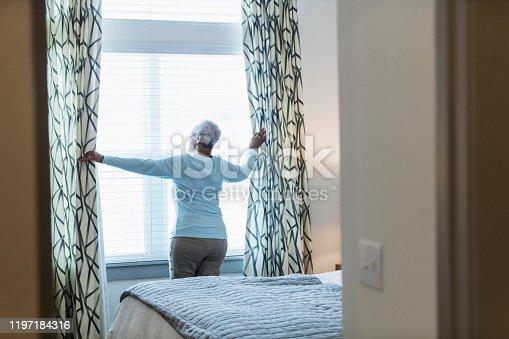 949450544 istock photo Senior African-American woman waking up, at window 1197184316