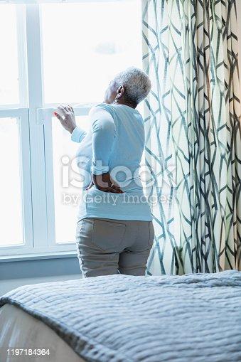 949450544 istock photo Senior African-American woman waking up, at window 1197184364