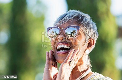 A beautiful senior African-American woman in her 70s wearing sunglasses on a sunny day. She is looking up at the sky, amazed by what she sees, hands touching her chin. A building, palm trees and clear blue skies are visible in the reflection in the sunglasses.