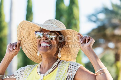 A beautiful senior African-American woman in her 70s wearing sunglasses and a wide brim hat on a sunny day. She is looking up at the sky, smiling. A building, palm trees and clear blue skies are visible in the reflection in the sunglasses.