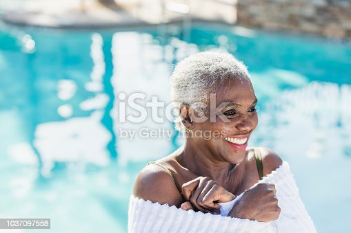 A senior African-American woman in her 60s wrapped in a towel by a swimming pool, smiling.