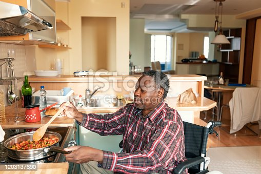 Disabled Afro-American Person is Enjoying in Preparation of Delicious Lunch. A Senior African is Cooking a Dinner in Domestic Kitchen.