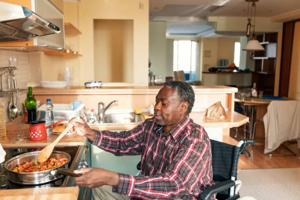 Senior Afro-Américain en fauteuil roulant prépare un déjeuner à la maison - Photo