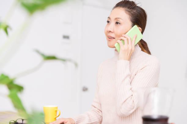電話で話す年上の女性 - people of color ストックフォトと画像