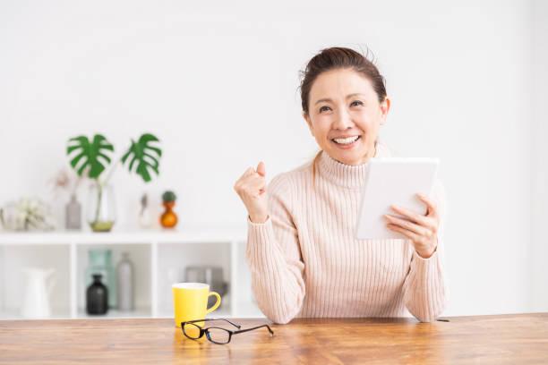 タブレットコンピュータを使用するシニア年齢の女性 - ライフスタイル ストックフォトと画像
