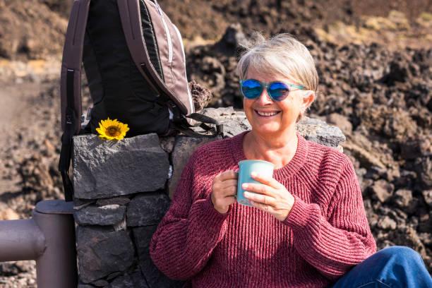 senior år attraktiva tredje ålder kvinnan leende och njuta av utomhus semester resa med ryggsäck att känna friheten och självständigheten från samhället – dricka te och bo glad besöker världen - happy indie pop bildbanksfoton och bilder