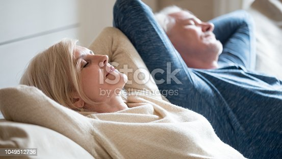 1143763067istockphoto Senior aged couple relaxing on comfortable sofa together breathing air 1049512736