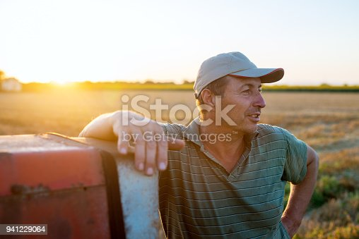 Senior agronomist man standing in a field leaning against old tractor after harvest at sunset.