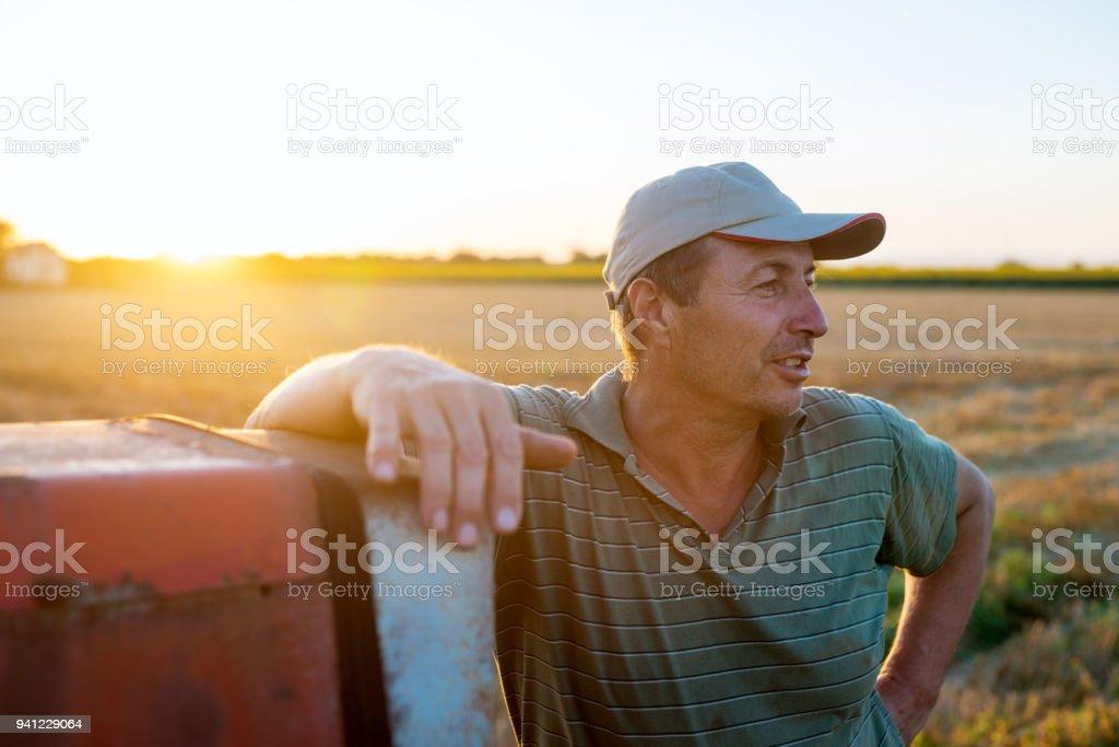 古いトラクターに日没で収穫後のフィールドもたれ立っている男の人が上級農学者。 ストックフォト