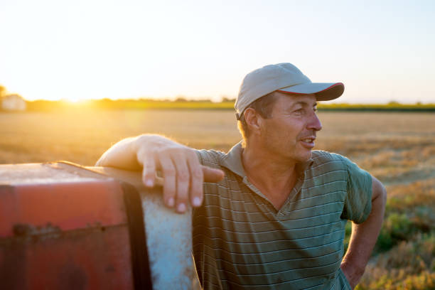 senior agronomist man standing in a field leaning against old tractor after harvest at sunset. - farmer stock photos and pictures