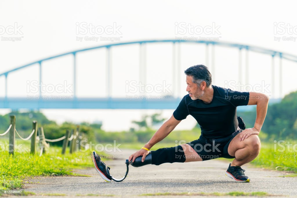 Senior amputee stretching before a run stock photo