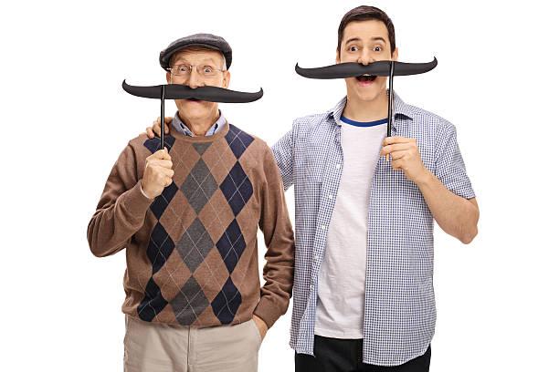 senior and a young man posing with big fake moustaches - riesenschnauzer stock-fotos und bilder