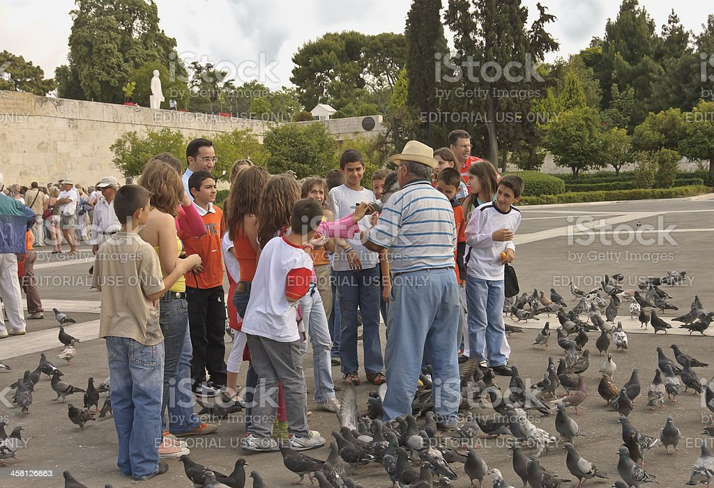 senior and children with pigeons stock photo