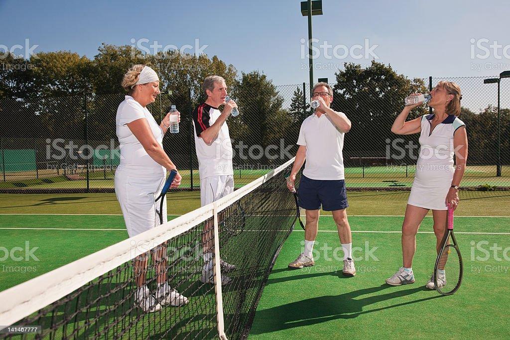 Senior and mature adults enjoying drink on tennis court stock photo