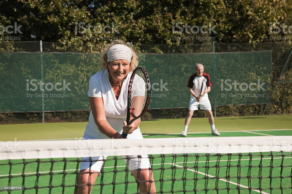 Senior and mature adults playing tennis stock photo