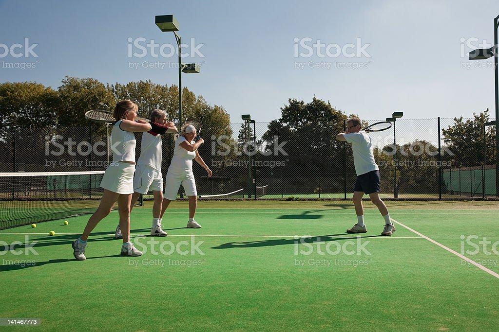 Senior and mature adults practising tennis stock photo