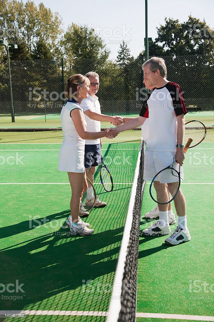 Senior and mature adults shaking hands on tennis court stock photo
