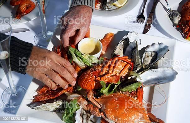 Senior And Mature Man Taking Prawns From Dish Of Shellfish Closeup Stock Photo - Download Image Now