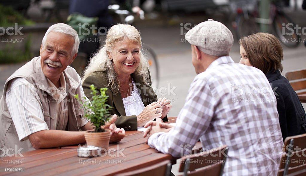 Senior und junge Paare lachen-Sitzung im Freien Kulisse der Stadt Lizenzfreies stock-foto