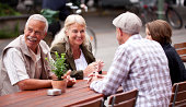 A senior and a young couple are enjoying a break in the city, sitting on a table outside. The senior couple is facing the camera, both laughing. Selective focus on the senior couple.