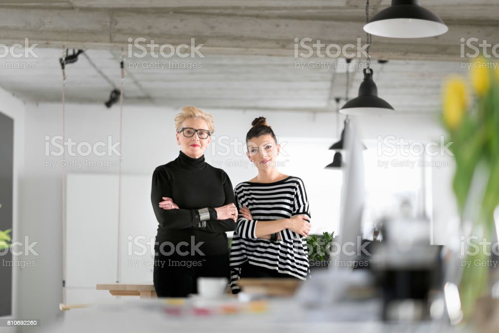 Senior and young designers in the studio Creative senior and young woman standing in the office, smiling at the camera. 60-69 Years Stock Photo