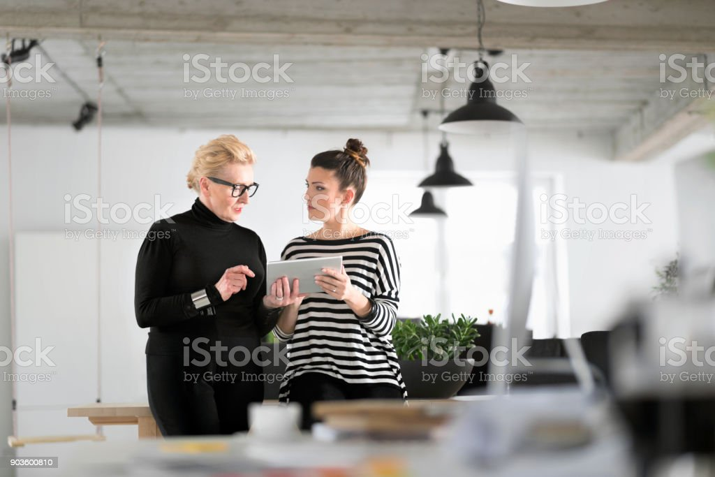 Senior and young designers in the studio Creative senior and young woman standing in the office and using a digital tablet together. 60-69 Years Stock Photo