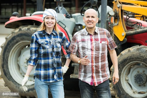 istock Senior and young farmers working at machinery 646435364