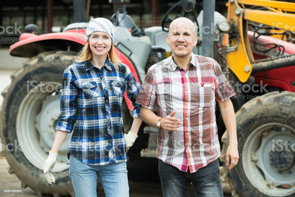 Senior and young farmers working at machinery stock photo