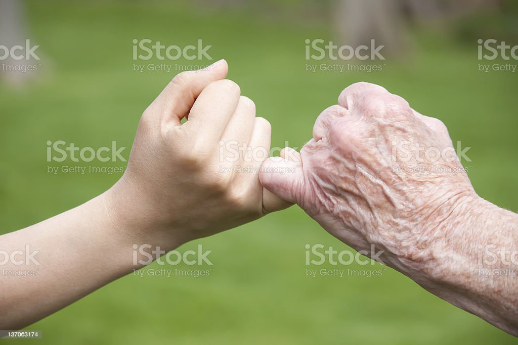 Senior and Young Hands Promise stock photo