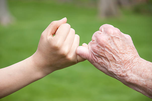 senior and young hands promise - pinky promise stock photos and pictures