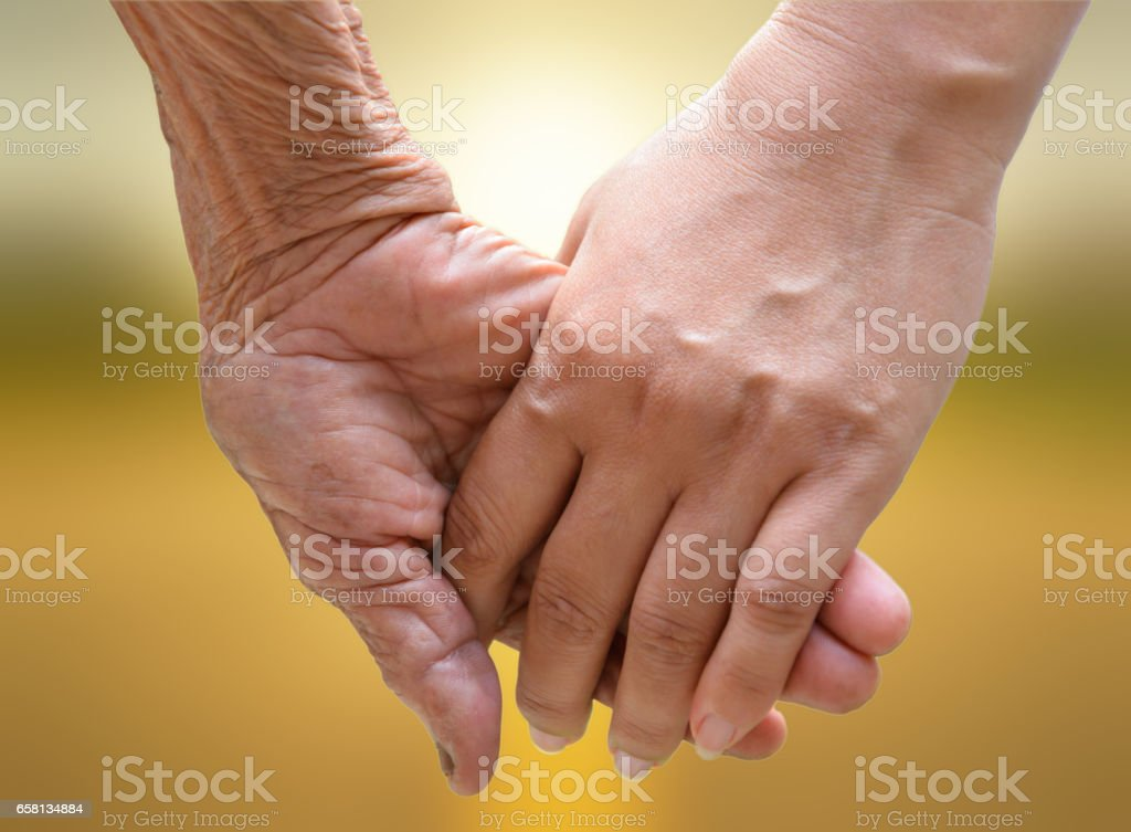 Senior and young holding hands at sunset. royalty-free stock photo