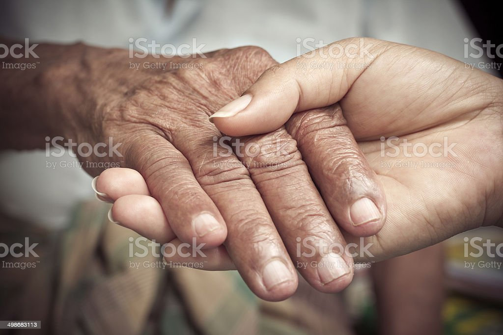 Senior and young holding hands stock photo