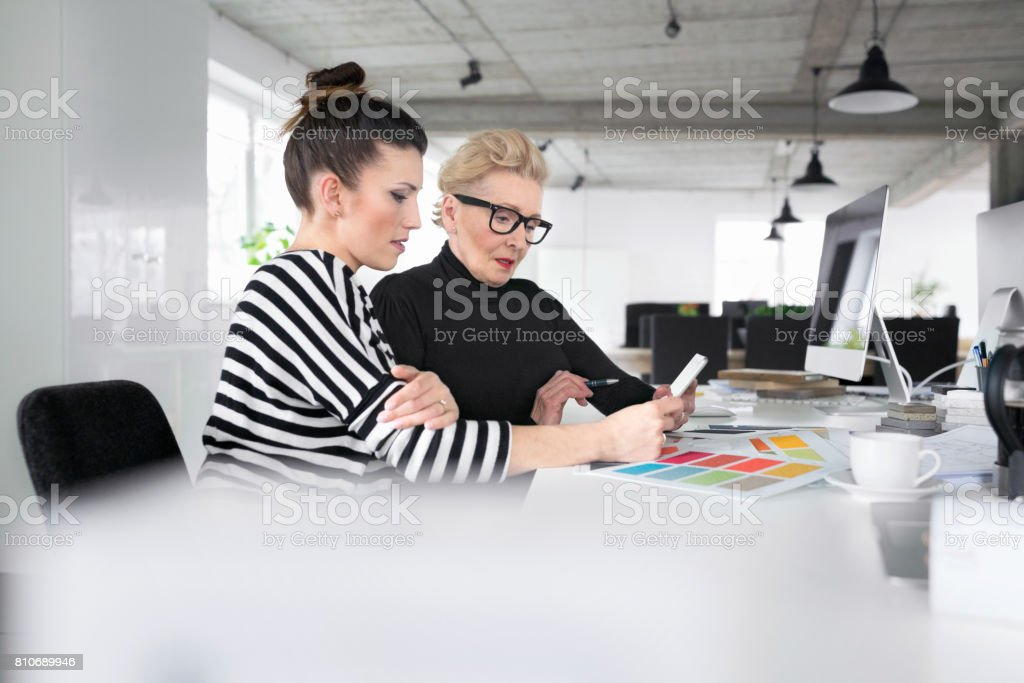 Senior and young interior designers using a digital tablet in the office Senior interior designer working together with young woman in the office, sitting at the desk and using a digital tablet together. 60-69 Years Stock Photo
